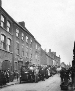 The premises of Eyland & Sons is to the left on this picture which shows the work staff about to depart on a trip to Evesham.