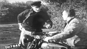 "A still taken from the film which shows two of the ""baddies"" and a Walsall registered B.S.A. motorbike."
